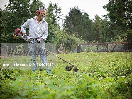Man trimming weeds in garden