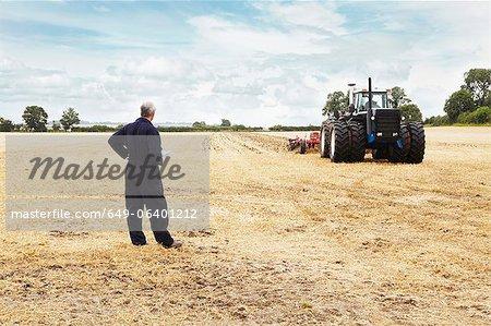 Tracteur surplombant d'agriculteur dans le domaine de la culture