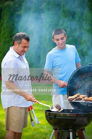 Père et fils, grillades en plein air