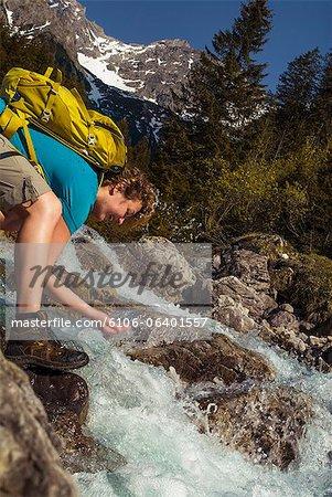 weibliche Wanderer erfrischend mit Wasser in Bergen