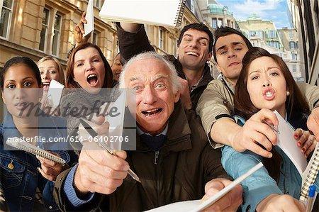 Groupe de gens qui demandent des autographes