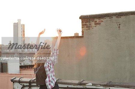 Jeune femme, écouter de la musique avec les bras levés sur les toits de la ville