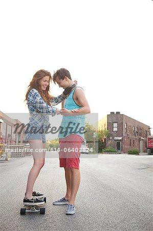Jeune femme sur planche à roulettes avec son petit ami