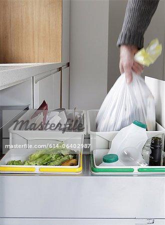 Personne enlever le sac à ordures provenant des déchets et le recyclage de tiroir