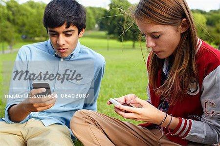Adolescent et jeune fille à l'aide de smartphones