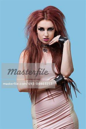 Portrait de jeune femme funky debout de longs cheveux sur fond bleu