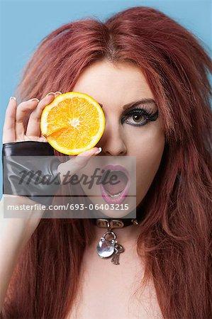 Portrait de jeune funky couvrant les yeux à l'orange en tranches sur fond bleu