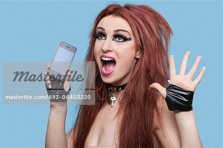 Portrait de funky jeune femme crier pendant l'utilisation de téléphone portable sur fond bleu