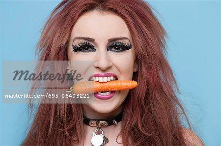 Portrait de funky jeune femme tenant des carottes de bouche sur fond bleu