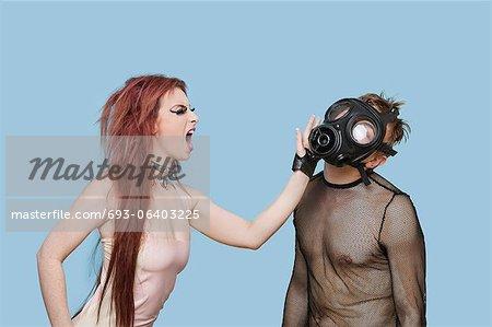 Funky jeune femme frappant l'homme au masque à gaz sur fond bleu