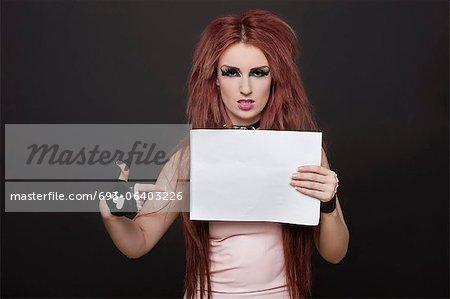 Portrait de l'arrogante jeune femme funky pointant vers une plaque vierge sur fond noir