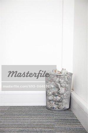 Wastebasket full of crumpled paper in corner against white wall