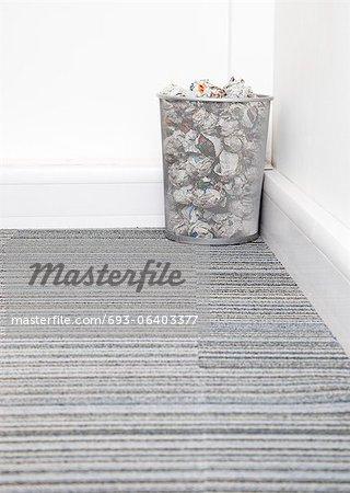 Wastebasket full of crumpled paper in corner on carpet floor in room