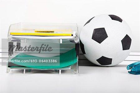 Fußball in der Nähe von Datei-Rack am Schreibtisch