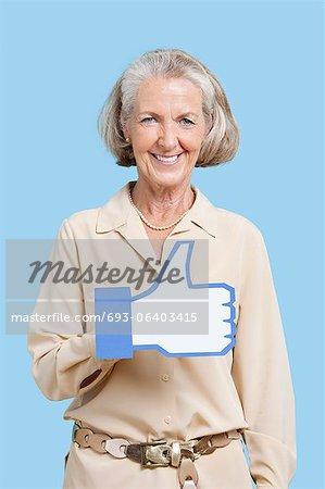 Portrait de femme senior en employés occasionnels holding faux comme bouton sur fond bleu