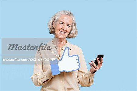 Portrait de femme senior avec téléphone portable maintenant faux comme bouton sur fond bleu