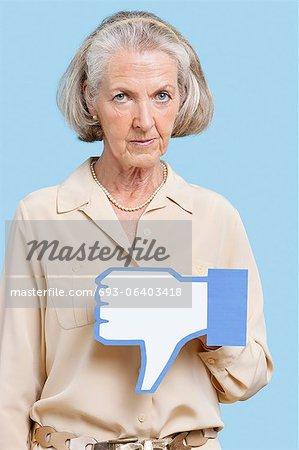 Portrait de femme senior avec aversion faux bouton sur fond bleu