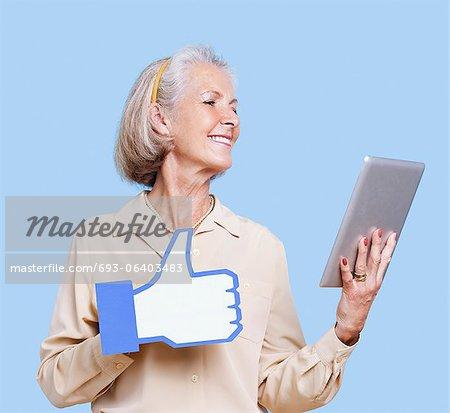 Femme Senior avec tablet PC maintenant faux comme bouton sur fond bleu