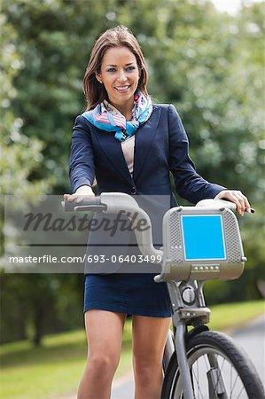 Jeune femme d'affaires ayant qualité pour agir au parc de vélo