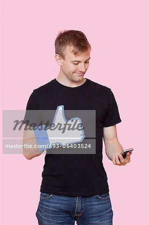 Jeune homme avec téléphone portable maintenant faux comme bouton sur fond rose