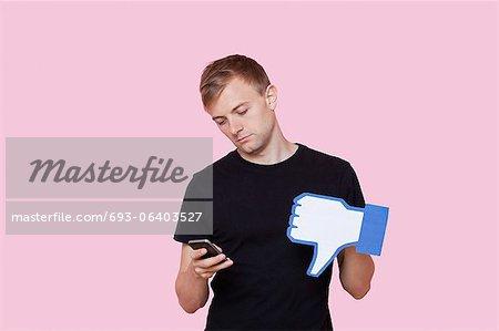 Jeune homme avec téléphone portable maintenant faux n'aiment pas le bouton sur fond rose