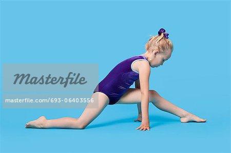 Jeune fille en Body étirer les jambes sur fond bleu