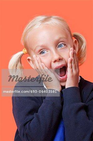 Überrascht junge Schulmädchen mit den Händen auf das Gesicht über orange Hintergrund
