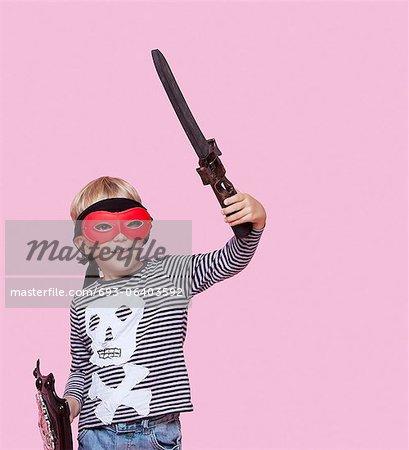 Glückliche junge Augen Maske Betrieb Schwert und Schild tragen, auf rosa Hintergrund