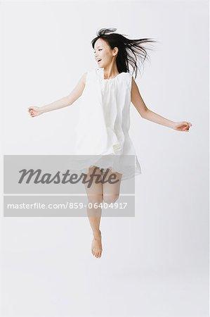 Asiatische Frau in einem weißen Kleid springen