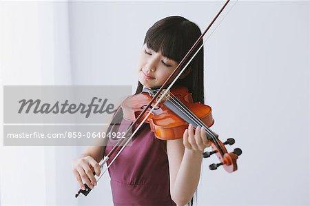 Asiatische Frau in einem lila Kleid Geige spielen