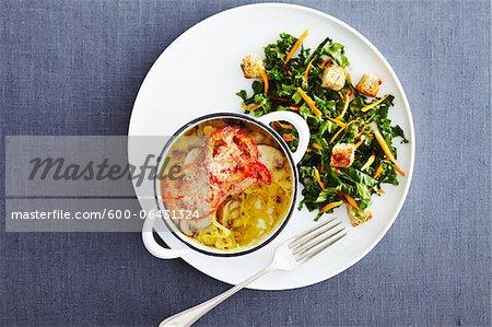 Vue de salade et de Casserole sur la plaque avec une fourchette sur fond bleu en Studio