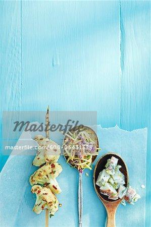 Vue de chou-fleur grillé sur la visseuse et cuillères rempli de salade sur du papier ciré sur une Table en bois bleue en Studio