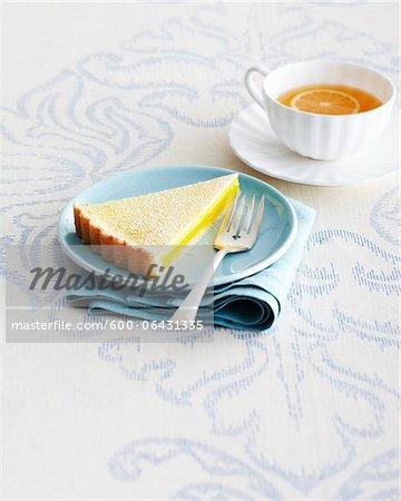 Scheibe Lemon Tart und Gabel auf blauen Platte mit Tasse und Untertasse von Kräutertee auf Tischdecke im Studio