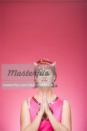 Portrait of Woman Wearing Devil Horns Praying
