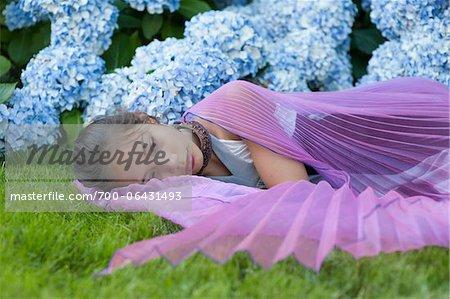Girl Wearing Fairy Wings Lying Down Outside in Flower Garden