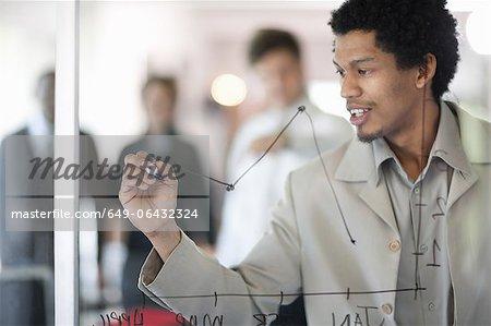 Businessman drawing graph on window