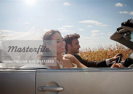 Couple de jeunes mariés en Cabriolet
