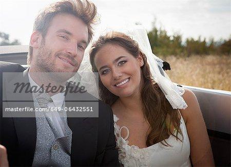 Couple de jeunes mariés assis en Cabriolet