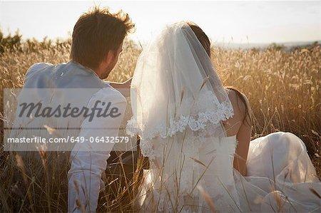 Couple de jeunes mariés, assis dans l'herbe haute