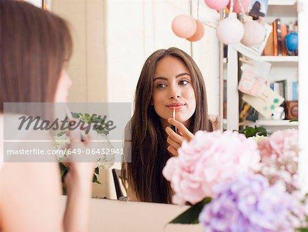 Woman applying make up Spiegel