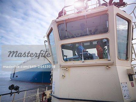Workers sitting in tugboat wheelhouse