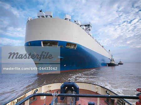 Remorqueur poussant grand bateau à la mer