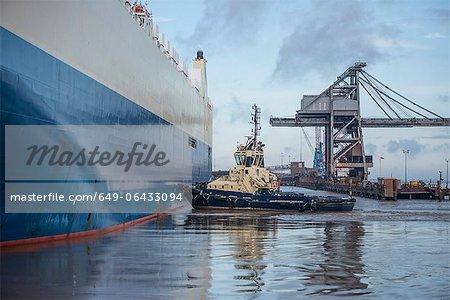 Tugboat pushing ship in harbor