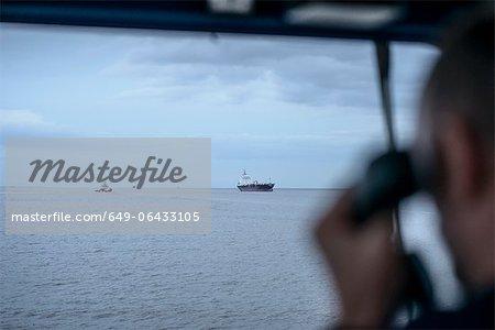 Worker on tugboat talking on phone