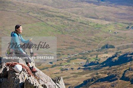 Weibliche Felsenkletterer sitzend auf einem Felsvorsprung, mit eine Pause