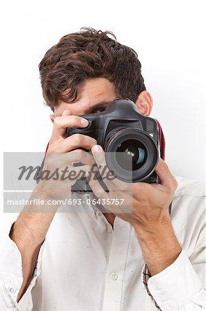 Junger Mann nehmen Foto mit Jahrgang Kamera vor weißem Hintergrund