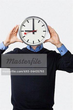 Jeune homme couvrant son visage avec commandes horloge sur fond blanc