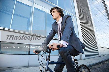 Vue d'angle faible de vélo jeune entrepreneur en construisant