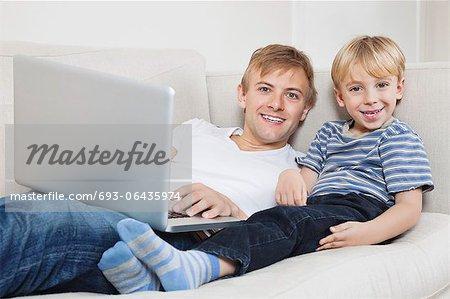 Portrait de garçon heureux père utilise un ordinateur portable sur le canapé