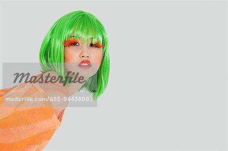 Porträt der jungen Frau, der grüne Perücke über den grauen Hintergrund